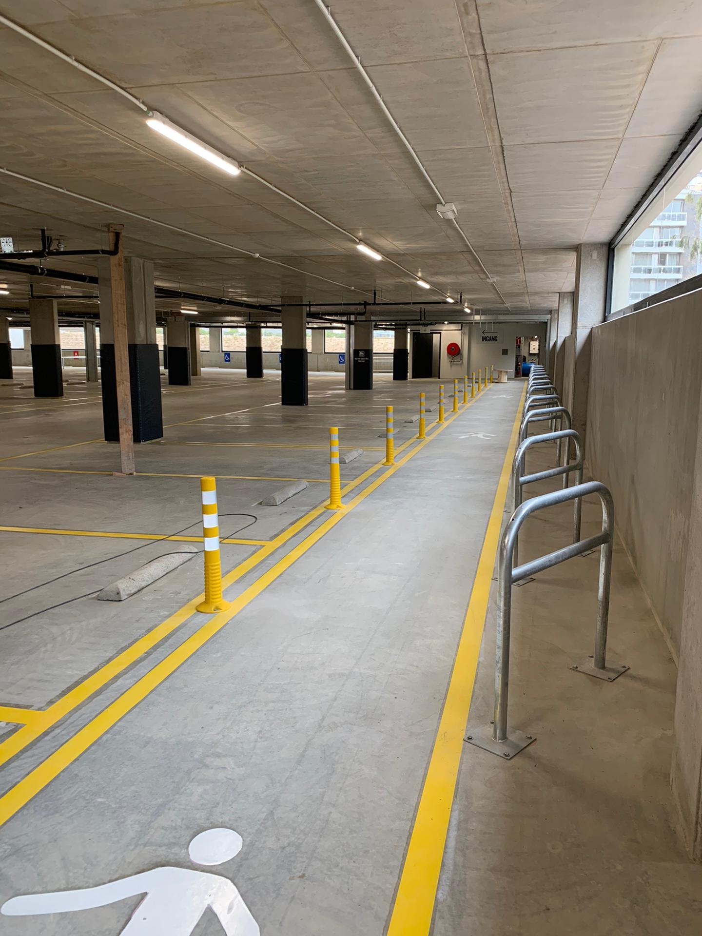 Binnenbelijning parkeerplaatsen, wandelpaden en fietspaden, kickback palen en stalen veiligheidshekken aanrijbeveiliging, bij Delhaize Aalst, door Remotec