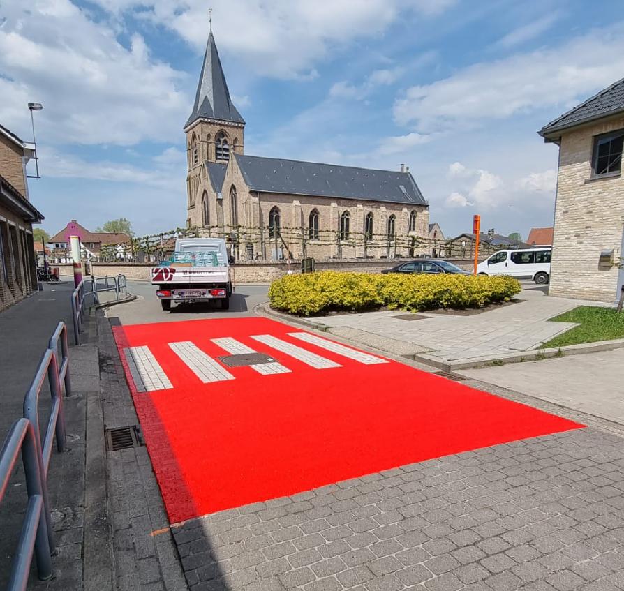 Buitenbelijning wegmarkering zebrapad aan school, extra opvallend door rood vlak, verkeersveiligheid, wegmarkeringen door Remotec